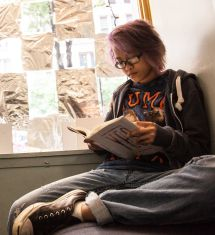 Teen_girl_reading_YOUmedia-215x235